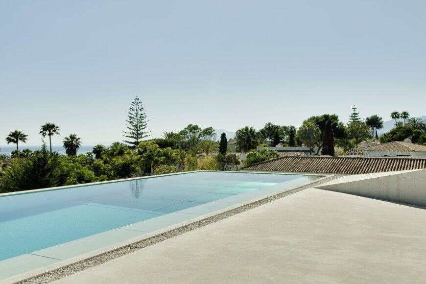 This swimming pool looks out over the gorgeous tropical landscape surrounding the house. A loose gravel boarder around the edge of the pool acts as drainage for any water overflow.