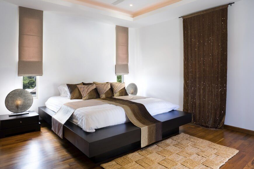 A minimalist room like this one does not need a headboard to weight it down. The heavy wood of the bed frame is enough to weight down this bright space. A dark wall hanging and thick textures add more interest to the space.