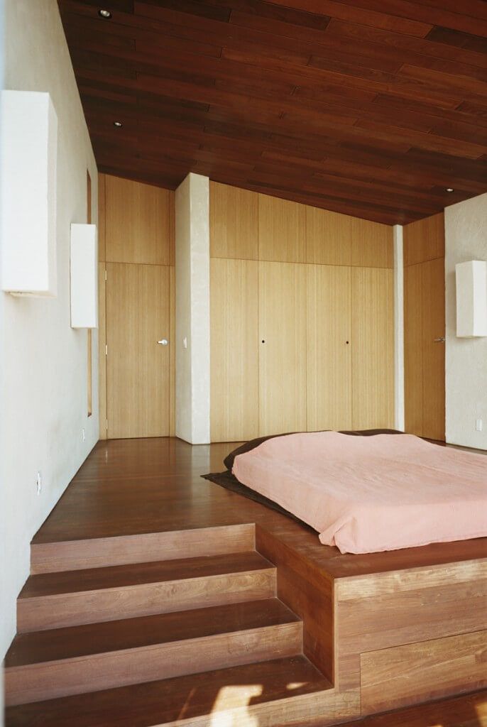 This streamlined, minimal bedroom contains plenty of storage hidden from view. Including a headboard here would take away from the clean lines of this lovely, simplistic design.