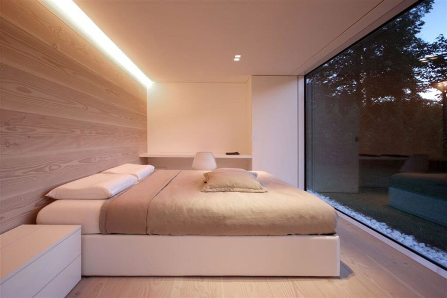 This lovely minimalist bedroom allows the view of the outdoors to play the showcase for the room. Sleek lines and low profile furniture keep the zen-like low key vibe of the room, which would be taken away from with anything but the wood accent wall.