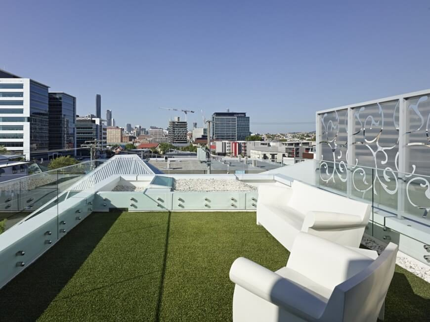 A Beautiful Modern Urban Rooftop Patio With Faux Grass. The Small Patio Is  Completely Surrounded