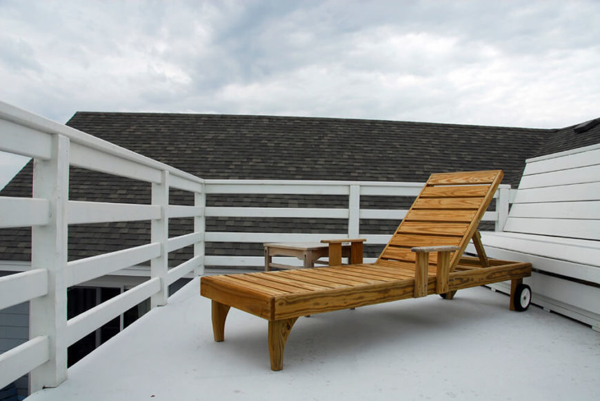 A small deck with a built-in bench and a lounge chair arranged on the white concrete patio. The patio is surrounded by a tall white fence.
