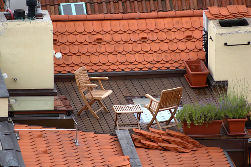 A rooftop patio with several small container planters and a small, intimate seating area between two sections of terra cotta roof.