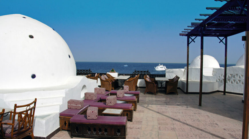 A lovely rooftop patio overlooking a large body of water with yachts in the background. Curved domes dot the patio.