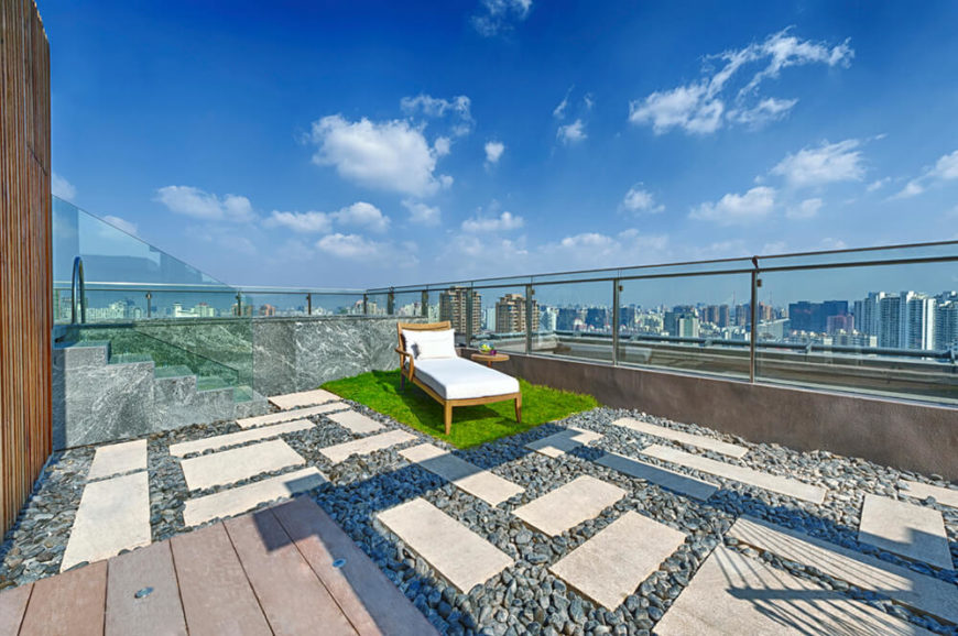 A Larger Rooftop Patio Will Tall Glass Balustrades And Stone Steps. The  Patio Is Sectioned