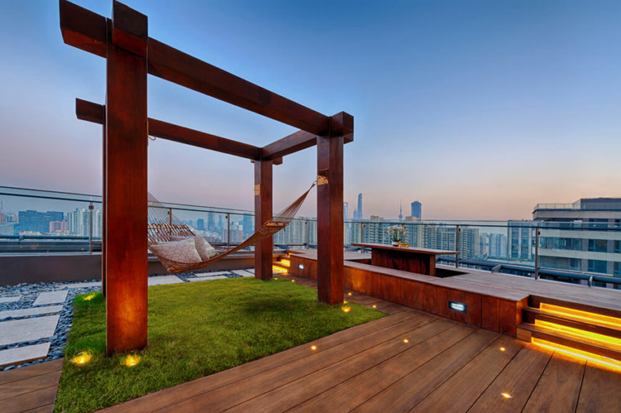 A breezy Zen-style rooftop patio with a built-in dining table, lighted steps, a glass balustrade, and a hammock complete with supports.
