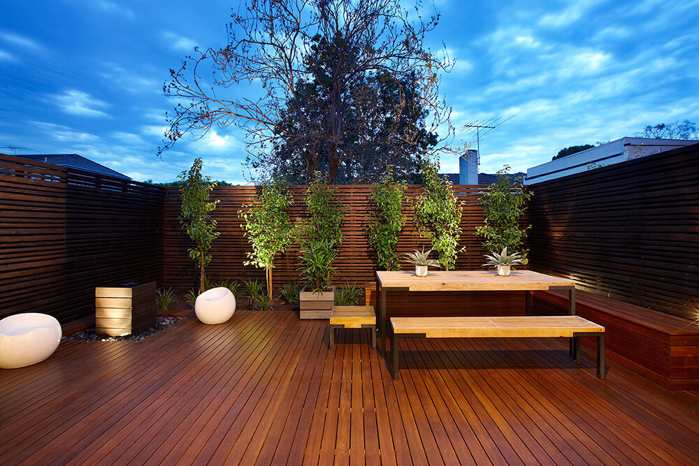 Rustic style deck featuring a lovely dining table set and romantic lights.