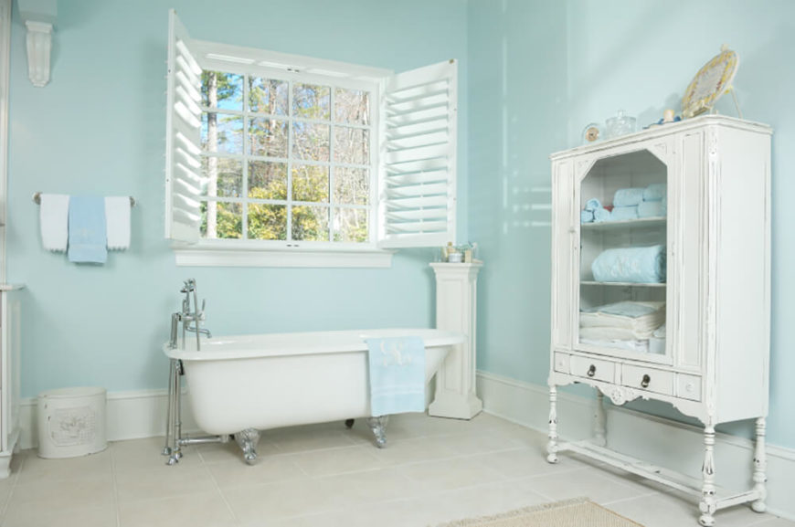 Dual shutters open up to let natural light flood in through this window. A clawfoot tub sits directly beneath the window. Baby blue walls and accent towels combined with the white floor and utilities make this space bright and welcoming.