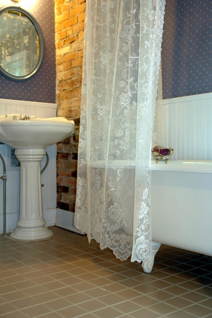 This small bathroom space is accented by a corner of wall featuring brick instead of wallpaper. The clawfoot tub has the added option of privacy, due to a elegant curtain hanging from the ceiling.