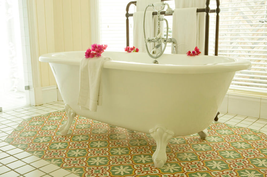 This large clawfoot tub sits centered on a patch of accent tiles, with a different design pattern from the surrounding floor. The windows surrounding the tub provide natural lighting for the room.