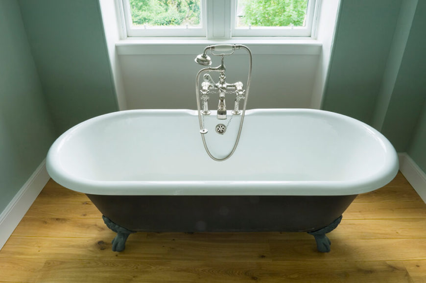 This clawfoot tub is fit for two, and sits upon a lightly stained hardwood floor. The tub is centered beneath a double pane window and is illuminated by the natural light spilling into the room.