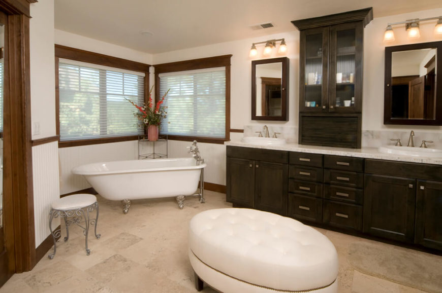 This spacious bathroom features a large countertop with two sinks and a space in between for storage and functional use. There is a large upholstered ottoman that provides seating, as well as a small stool off to the side. A clawfoot tub is featured in the corner beneath two large windows.