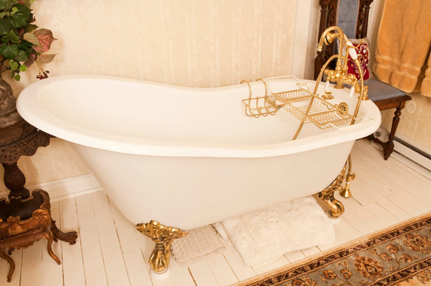 A clawfoot tub with golden accents sits upon a white tile floor, with what appears to be a large area rug covering the majority of the floor space. A small table beside the tub holds decorative plants that compliment the wallpaper in this bathroom.