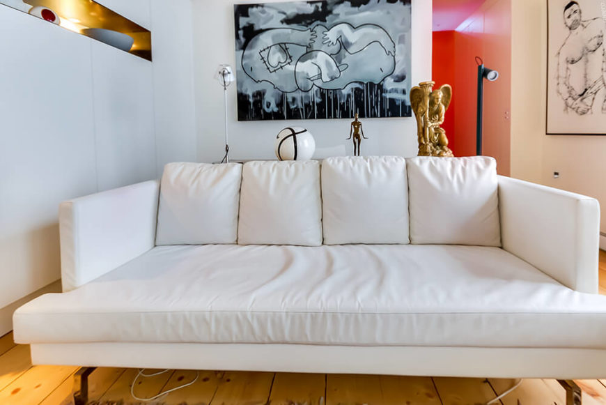 In this space, the idiosyncratic and fascinating artwork is the dominant stylistic feature, highlighted even more so by the lack of color in the surroundings. The clean white and natural wood surfaces make the perfect backdrop for personal touches.