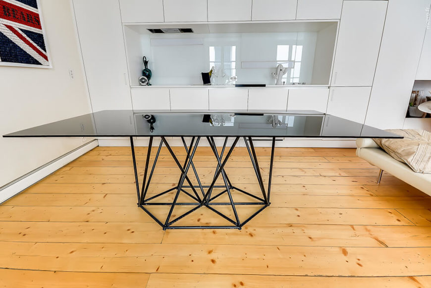 The dining table is a singularly defining element, a broad plane of black glass over a black steel frame. This obviously works in strong contrast with the white walls, while also anchoring the kitchen and dining area as distinct within the open room.