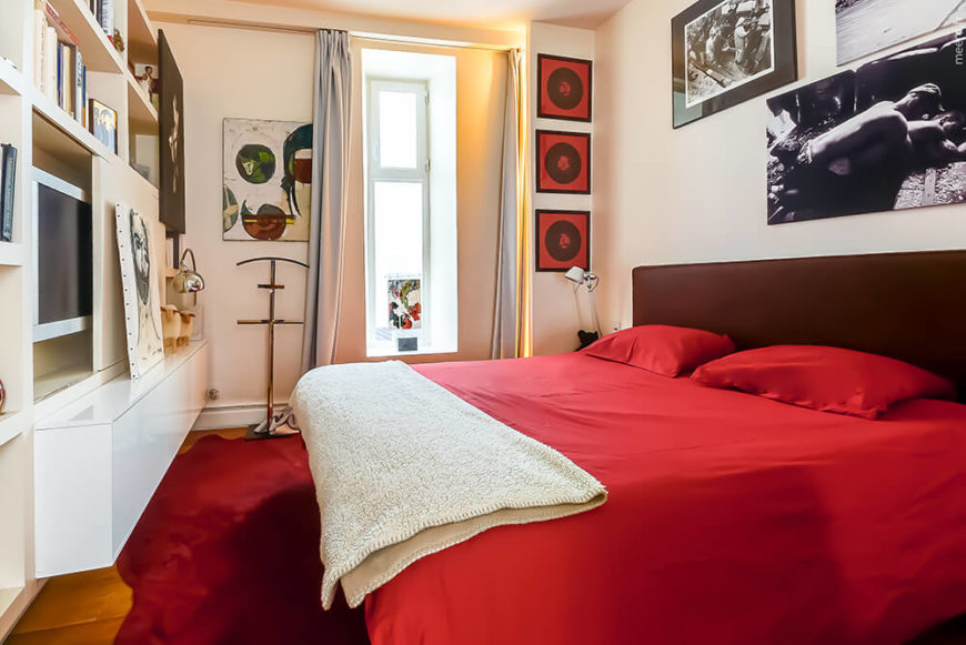 The bedroom is awash in bold red, including the bed, area rug, and paintings on the wall to the left of the tall window, we see built-in sleek white shelving with a sliding panel that reveals a television.