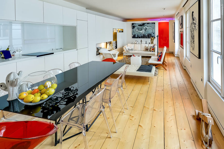 The living room end of this open space is clearly delineated by a backless sofa in white, with the kitchen and dining functions taking place in the foreground. At the far end, a red glass panel denotes the bathroom area.