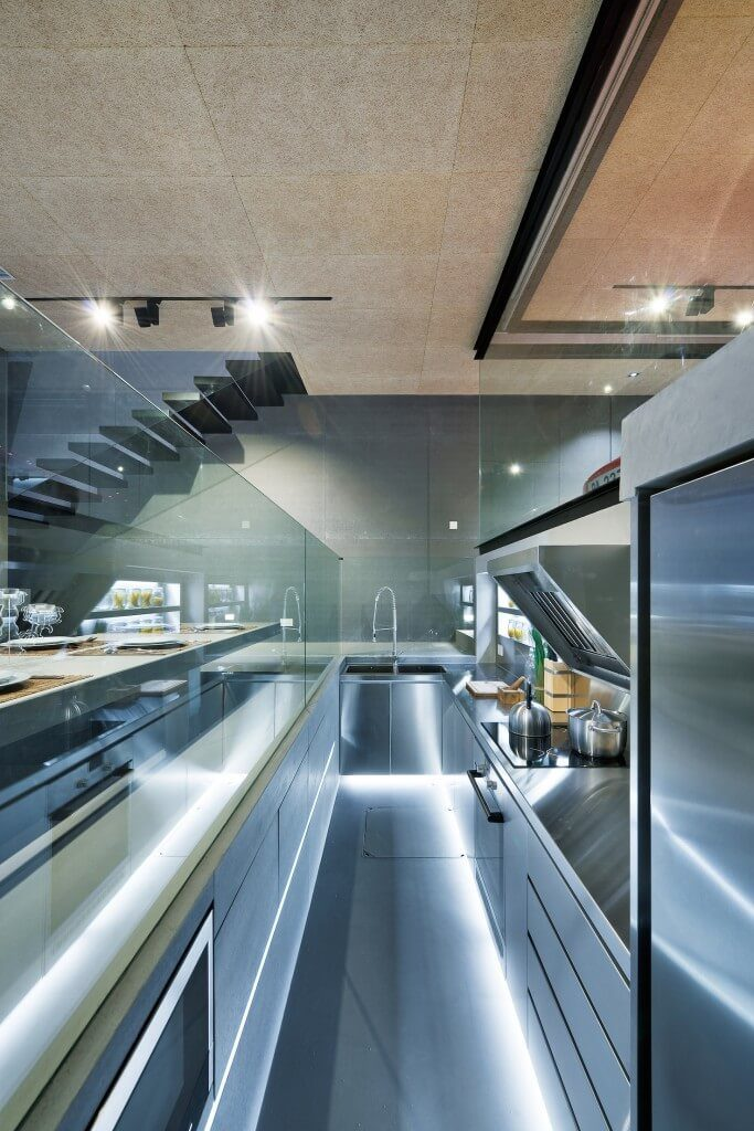 Another ultra-sleek stainless steel sunken kitchen with a glass balustrade between it and the dining table beyond. This glass and stainless steel galley kitchen is a wonder to behold.