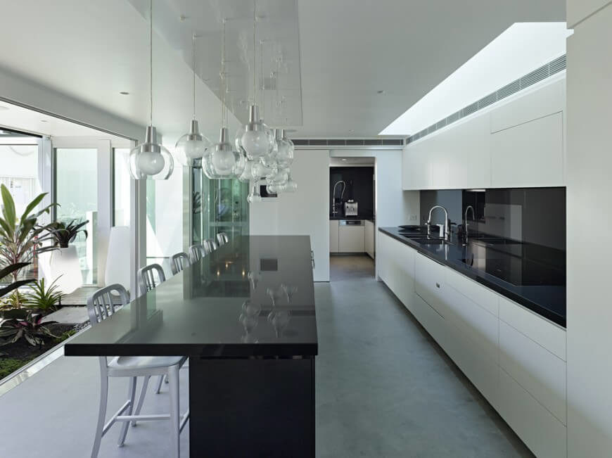 A modern kitchen in soft gray, pristine white, and glossy black with an indoor water feature and garden visible from the preparation area. A series of glass and chrome pendant lights hang above the eat-in kitchen island. Beyond the main kitchen is a pantry.