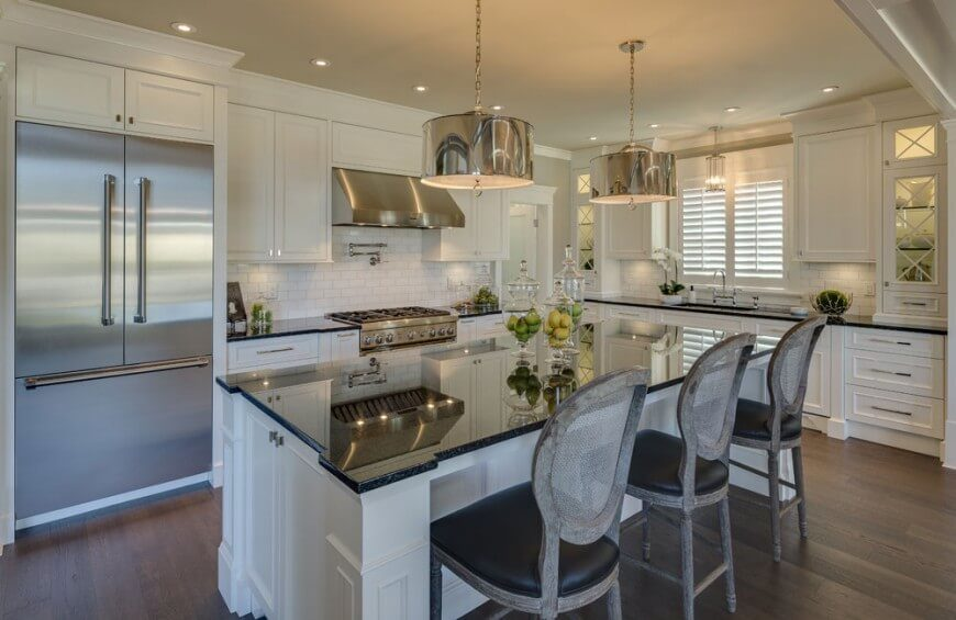 A luxurious white kitchen with stainless steel accents, a massive eat-in kitchen island, and backlit display cabinets on either side of the sink area. The chromed pendant lights above the island pull the stainless steel elements away from the back wall.