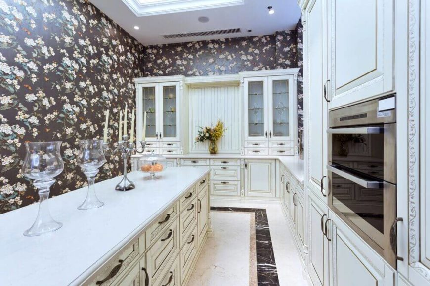 Rectangular kitchen with rich cabinetry and floral walls.