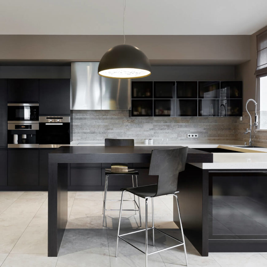 A rich contemporary kitchen that features a connected dining table for two, white countertops, and slim, small appliances built-into the wall cabinetry. A single large pendant light hangs above the intimate dining area.