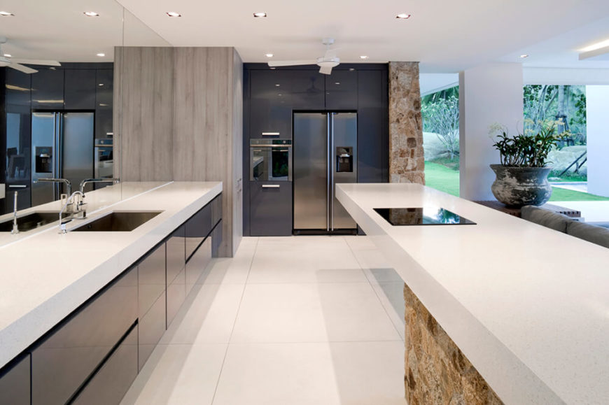 A beautiful and large rectangular kitchen with a mirrored wall to the left that allows the space to feel absolutely massive. Stone accent walls and a stone based island bring texture to this otherwise minimalist kitchen design.
