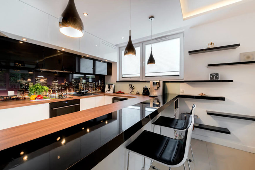 An interesting modern kitchen with an expanse of black countertops, shelving, and upper cabinets beside white floor cabinets and a butcher block countertop.