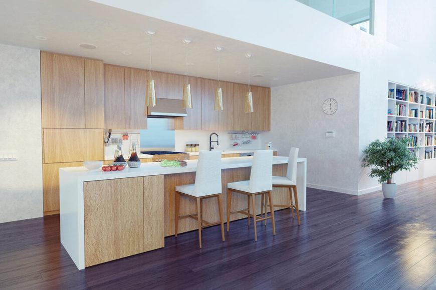 A lovely minimalist white and natural light wood kitchen with a contrasting dark hardwood floor. The kitchen area is contained beneath an alcove in the massive open-concept main living area.