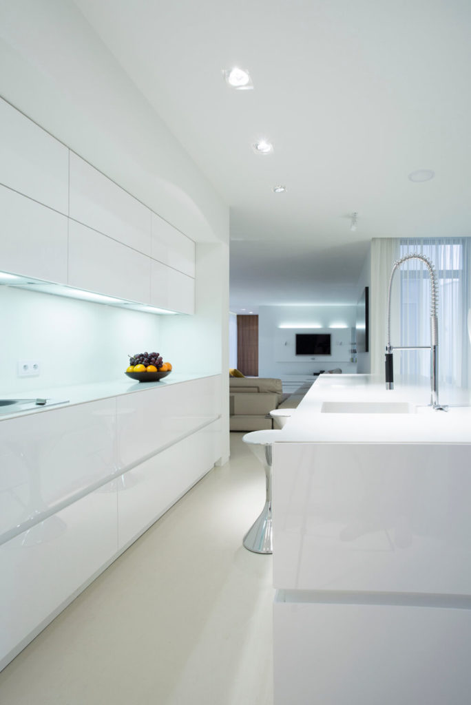 An all-white modern kitchen with a centered eat-in bar, an unusual choice in a galley kitchen. Under cabinet lighting and light colors make this space feel much larger than it is.