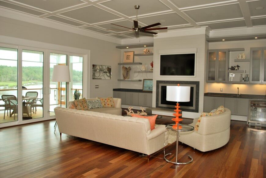 This living room features a rich hardwood floor, which helps to open up the space and keep everything looking fresh. The furniture all faces the entertainment wall, which features both a fireplace and a TV. On either side of the fireplace, you will see a counter with multiple shelving units, and on one side is a small sink to accommodate a mini bar.