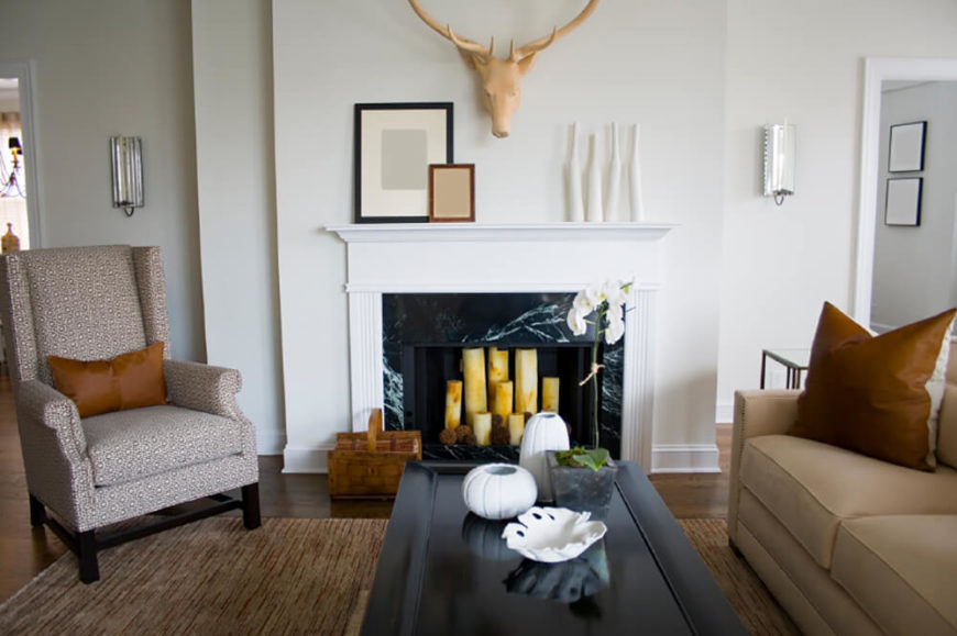 The stark white walls and mantle in this living room heavily contrasts the black marble fireplace and sleek black coffee table. Inside the fireplace, you will see some large candles, a creative display if you do not want to use real firewood. Above the mantle, an artificial animal mount accents the space and is the focal point for the room.