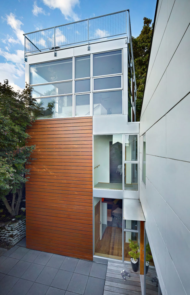 Even from the entryway, the front courtyard is incredibly private, as is the wood-encased tower. Large windows offer a peek into the upstairs hallway and the small breezeway