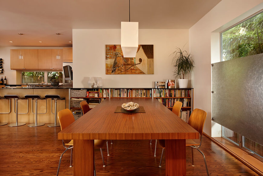 Upon entering the home, guests are greeted by an open-concept floor plan that includes a sitting area and the dining room as shown above. The rich hardwood table is surrounded by minimalist chairs. To the left is the family-style kitchen, which includes an entrance to the home office.