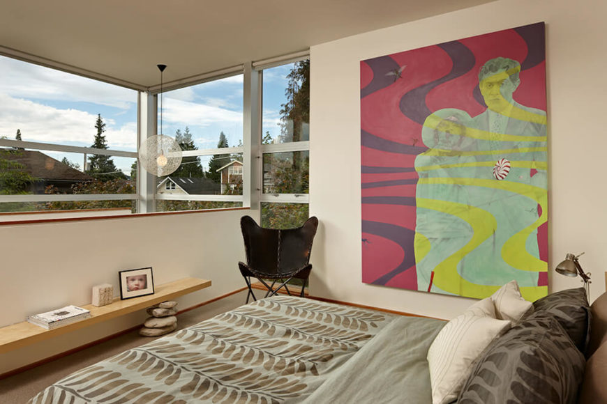 The third floor features the top half of the primary suite--the primary bedroom. Minimalist features,like a bench with stacked stone supports, a butterfly chair, and a bold piece of modern art are the focal points of the room.