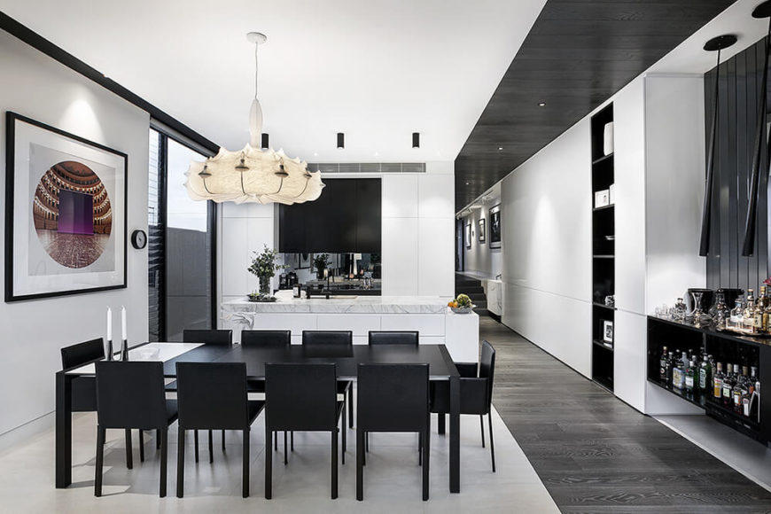 The dining and kitchen area is defined by light marble flooring, distinct from the muted grey hardwood seen throughout the rest of the home. The high contrast look is amplified by a black dining set and white kitchen cabinetry. To the right, an exquisite dry bar stands beneath modern pendant lights.