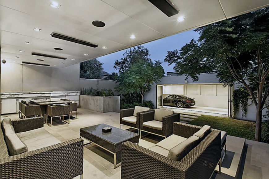 The patio features bespoke modern rattan furniture for both relaxing and dining purposes, plus a lengthy marble countertop with kitchen functions at the far left. Across the walk, we can see the showcase garage with folding glass panel access.