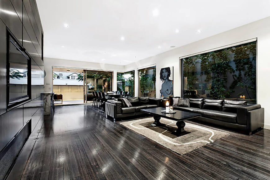 Sleek dark wood panels color the left wall, matching the hardwood flooring in contrast with the white walls and ceiling. At the far end we can see the dining set wrapped by full height windows.