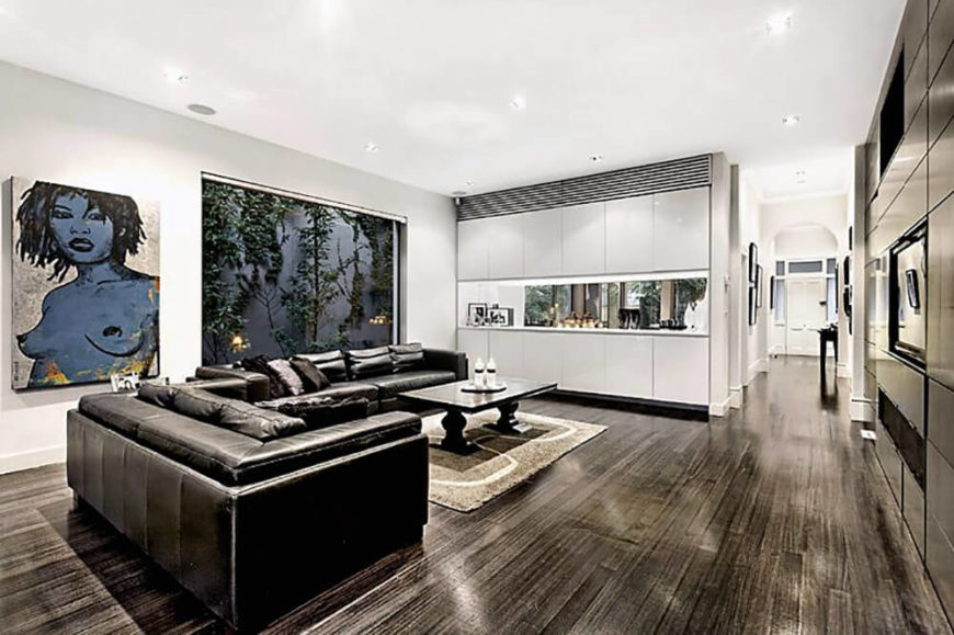 Here we are in the large open plan space, looking at the living room. A massive leather sectional defines the space, overlooked by a large window at left and artwork next to that. To the right, we can see down the main hall to the front entry.
