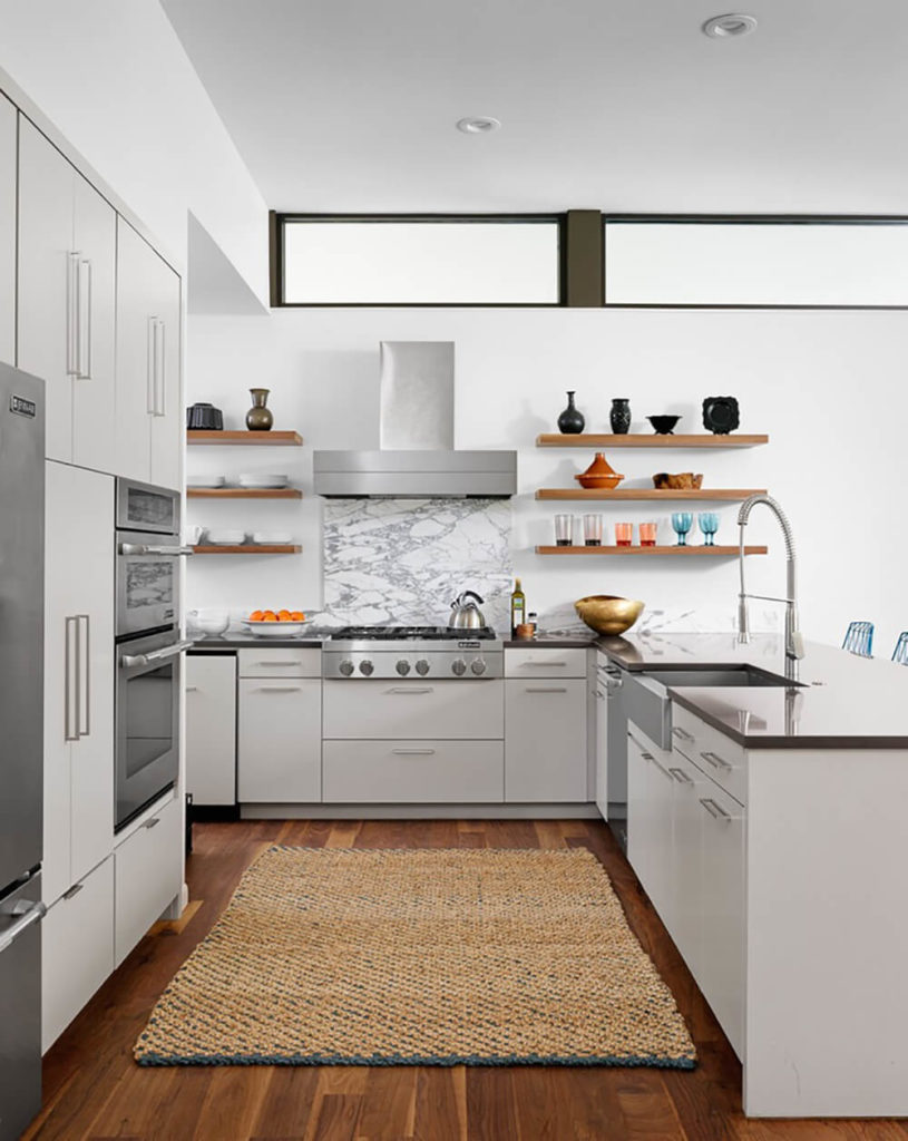 The kitchen is part of a larger open plan space, defined by its dark countertops over sleek white cabinetry. Above, a row of subtle windows sits just beneath the ceiling, naturally lighting the interior.