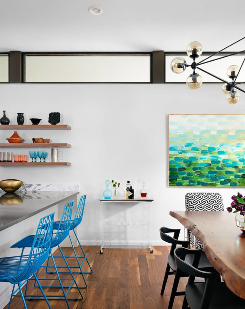 Next to the large countertop with in-kitchen dining space, and a row of bright blue chairs, we see the dining room table: a single piece of rich natural wood that offers a glimpse of organic curves in this thoroughly modern space.