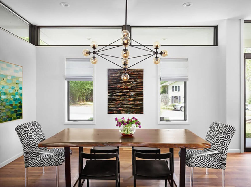 Above the dining table hangs a geometric wireframe chandelier, one of many unique touches in the home that bridge the gap between timeless and contemporary. The high contrast seating adds another lay of nuance to the setting.