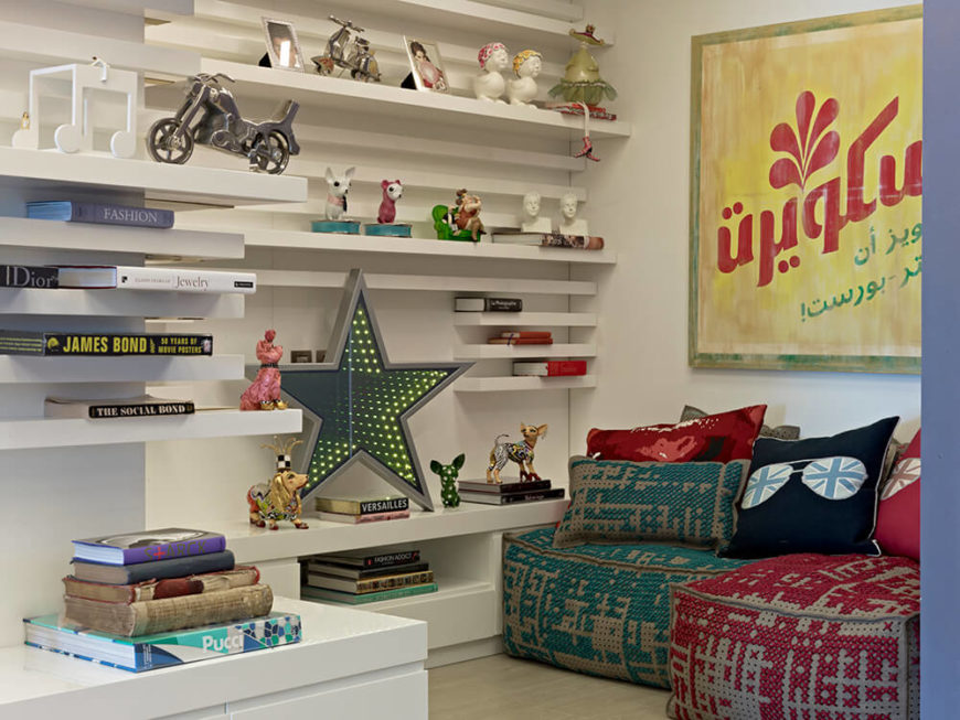 Across from the busier corner of the room, we see a set of built-in wall shelving dotted with books and nicknacks, floating freeform on a white wall.