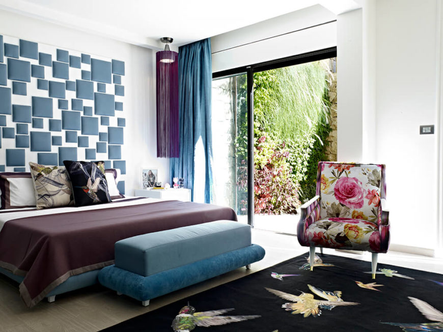 The master bedroom features a sliding glass door for direct patio access. A large black area rug features a hummingbird design, matching a decorative pillow on the bed itself.