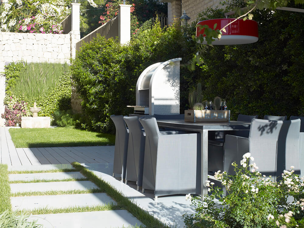 This home's outdoor kitchen located in the garden includes a modish dining table set.