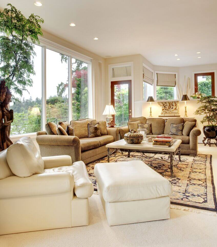 In this traditionally appointed living room, we see both textural brown sofas and a bold white leather armchair with matching ottoman in the foreground. With a set of wraparound windows, the whole room glows white.