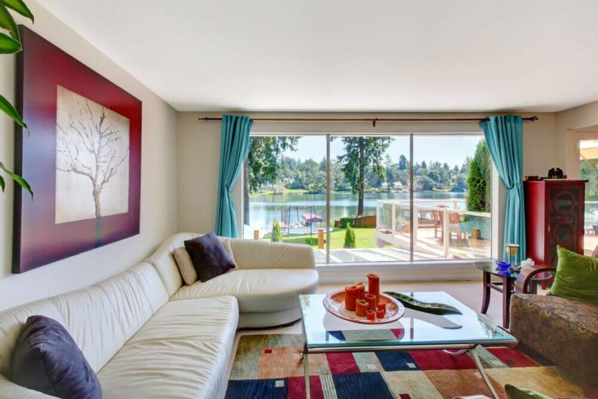 This lakeside home features massive windows for expansive aquatic views and allowing plentiful natural light inside. A lengthy white leather sectional wraps the colorful space over a patterned area rug.