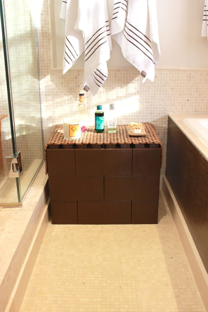 In a bathroom with limited shelf space, we see how the discreet brown blocks can be formed into a small hutch for display and easy access to necessary bathing products.