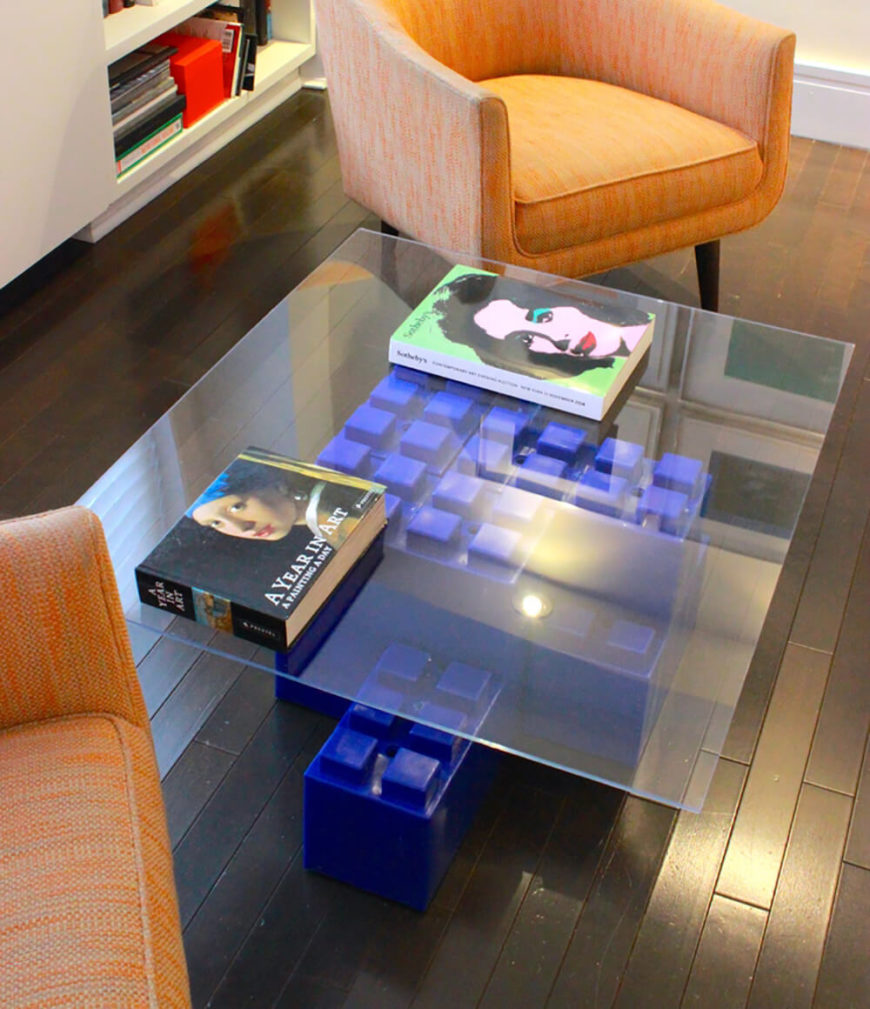 Here's a completely different coffee table configuration, using incremental block formations for a more svelte structure beneath the broad glass tabletop.
