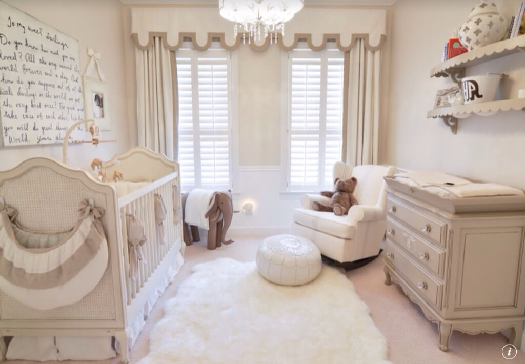 This nursery room features cute carpet flooring with a rug along with some shelves.